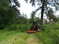 A tractor driving down a trail, mowing the vegetation on the trail.